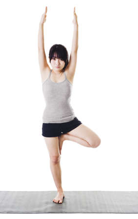 Chinese woman on a yoga mat doing the tree pose. photo