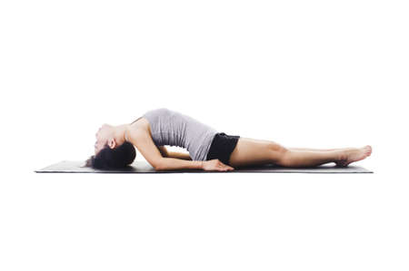 Chinese woman on a yoga mat doing the fish pose. photo