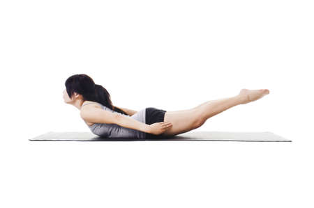 Chinese woman on a yoga mat doing the locust pose. photo
