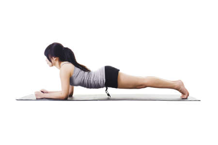 side pose: Chinese woman on a yoga mat doing the dolphin plank pose. Stock Photo