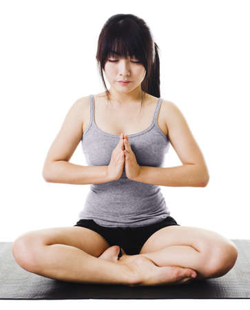 Chinese woman on a yoga mat doing the salutation seal pose. Meditation. photo