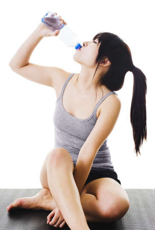 Chinese woman sitting on a yoga mat drinking water from a plastic bottle.