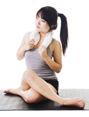 Portrait of a sitting Chinese woman holding a towel around her neck after a workout. photo