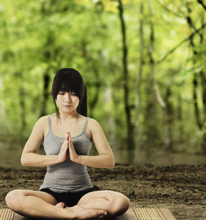 Asian woman on a yoga mat doing the salutation seal pose in a forest. Meditation. photo