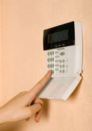 alarm button: Finger is touching the security system pad