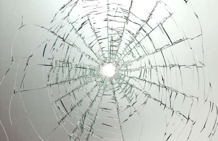 shatter: There is a broken car glass of windscreen with hole in picture center