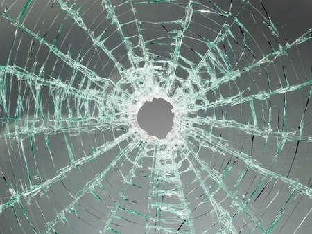 broken car: Hay un coche roto parabrisas de vidrio con agujeros en el centro de la imagen Foto de archivo