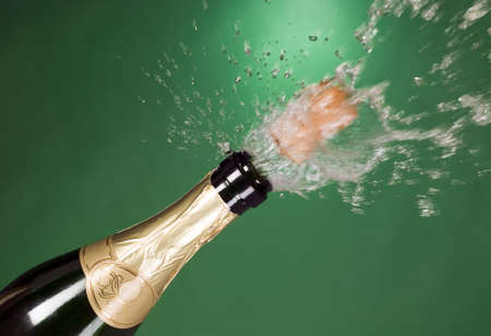 Explosion of green champagne bottle cork on background photo