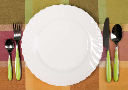 There are white plate with knife and fork on the table Stock Photo