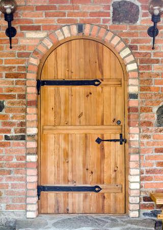 Brown door in old red brick wall Stock Photo - 7087318