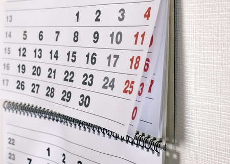 white walls: Calendar with dates of month is hanging on the wall