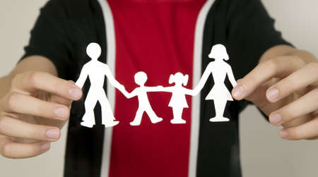Child with black and red shirts is holding family figures made from paper