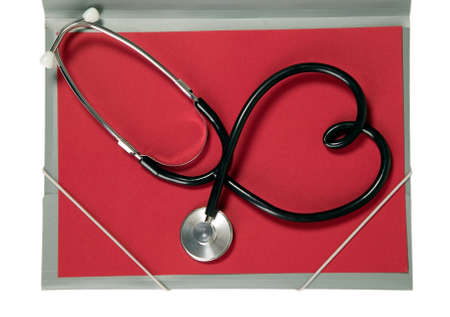A medicine stethoscope is lying on red paper photo