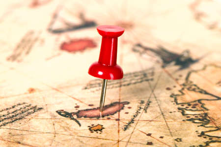 Thumbtack in the world map, close up, paper background photo