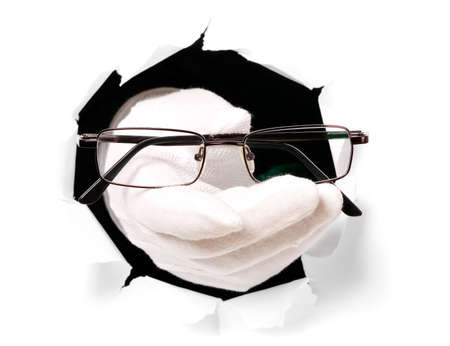 bifocals: Man with gloves is holding eyeglasses through a hole in white paper Stock Photo
