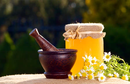 Jar of honey and wooden pestle with chamomiles on the table photo