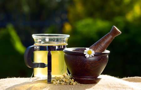 Wooden pestle with chamomiles and green tea on the table photo