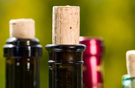 Red wine bottles with wooden corks on green background photo