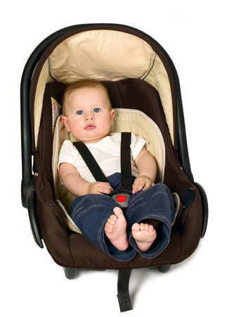 Baby boy is sitting in safety car seat Stock Photo