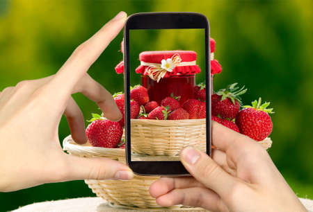hand basket: Man is taking photo of strawberries with smart mobile phone