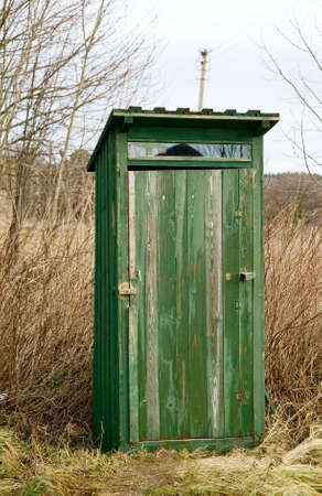 unsanitary: Green outdoor toilet near the field, unsanitary concept village