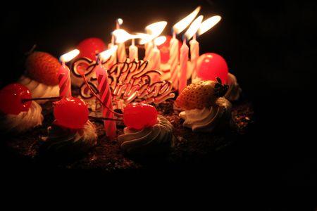 dark cherry: Birthday cake with lighting candles Stock Photo