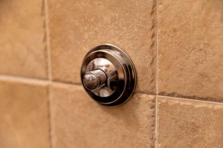 chrome bathroom flush button to drain the toilet on the wall Stock fotó