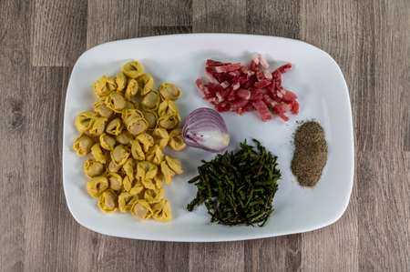 ingredients for cappelletti pancetta and asparagus creamed in a pan with parmesan