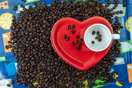 composition of coffee beans with heart shaped cup and saucer with ashtray and cigar