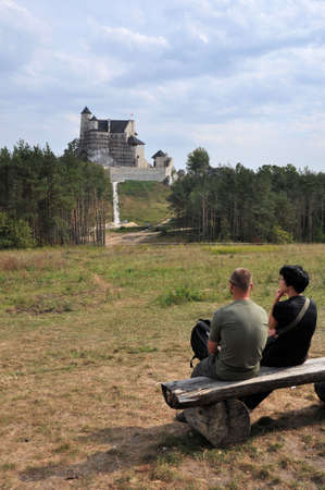 eagle nest rock: Bobolice, Poland, September 19, 2011 - Couple sitting on a bench, admiring renovated castle