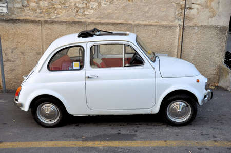 White Fiat 500 parked on italian street, side view