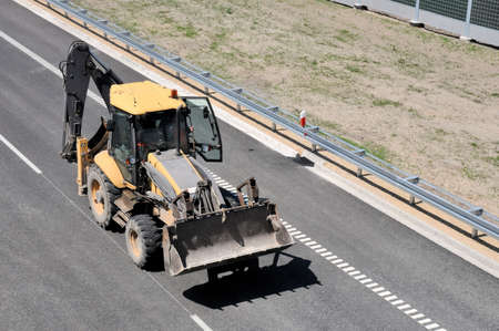 recently: Construction car - digger on recently finished highway Stock Photo