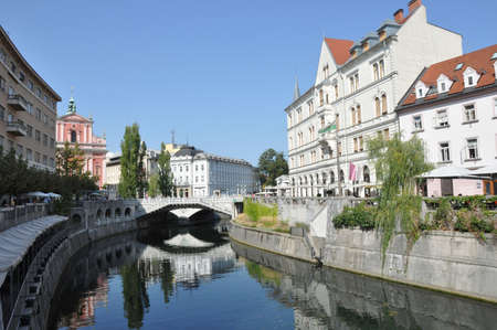 slovenia: Ljubljana city center and river Ljubljanica by day, Triple Bridge and The Franciscan Church of the Annunciation in the background