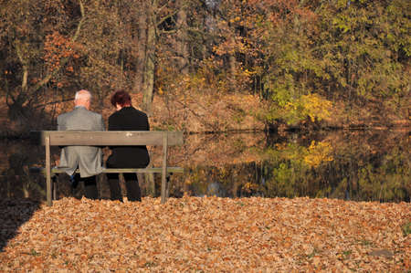 A senior couple sitting on a bench in park, surrounded by autumn leaves  photo