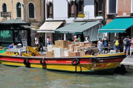 Venice - 18th of July 2012: DHL delivery boat with packages in canal of Venice. Delivery barges are the most common kind of utility vehicle in Venice Stock Photo - 17654372