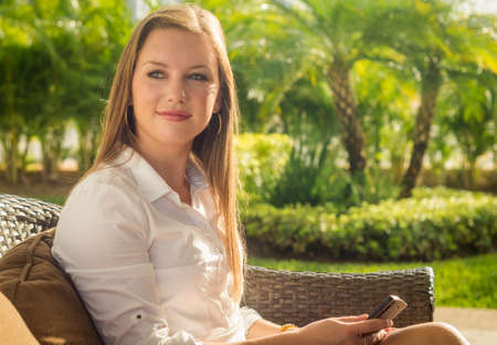 Danish beauty. Young white woman, blonde, blue eyes, long golden hair, white shirt posing in garden, outdoors under summer sun. Beautiful, cheerful, using the cell phone and looking at the landscape.