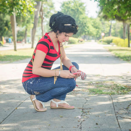 Cute white girl and black hair, look at her cell phone crouched on an old and broken sidewalk, with trees