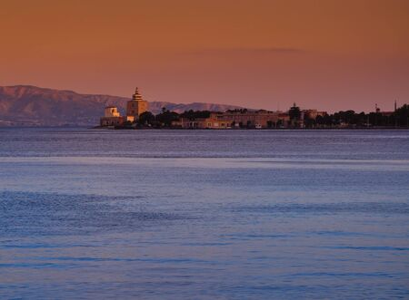 Messina harbor and lighthouse at sunset