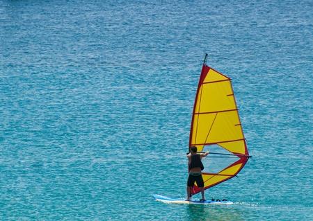 Giovane uomo fa windsurf nel mare di Sicilia Editorial