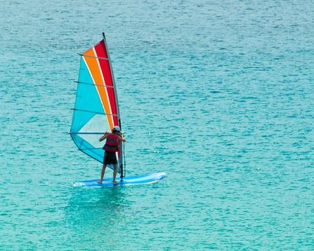 Giovane uomo impara il windsurf nel mare di sicilia