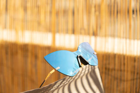 Futuristic Cat eye sunglasses designed for ladies with blue lens reflects the sunshine closeup. Selective focus