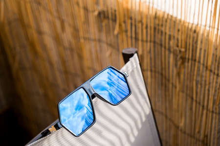 Aviator Sunglasses model for men with big blue lens reflecting the sun. Selective focus Zdjęcie Seryjne