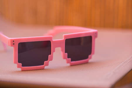 Pink pixel sunglasses model with black lenses closeup in a summer day. Selective focus