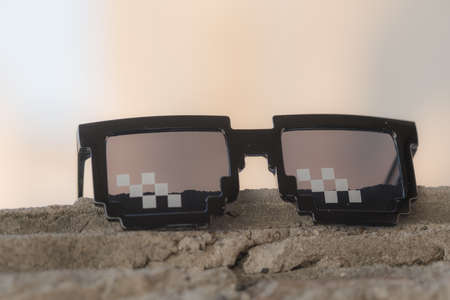 Black pixel sunglasses thug life with black lenses closeup. Selective focus