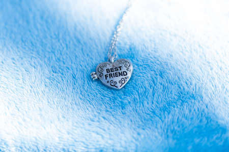 Pendant Best Friend heart necklace shoot outside in a summer day closeup. Selective Focus Banque d'images - 167025439