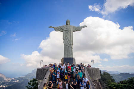 Rio de Janeiro, Brazil - July 13, 2017: Clear view of a crowd of tourists on top of the Corcovado mountain in Rio de Janeiro with the Christ statue towering over them and the landscape behind