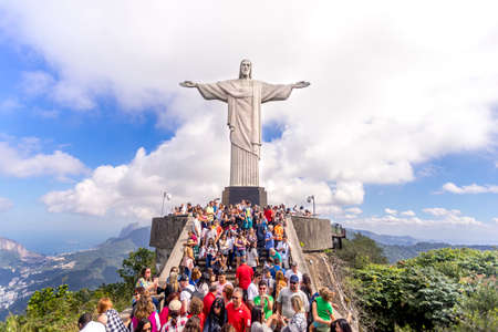 Rio de Janeiro, Brazil - July 13, 2017: Crowd of tourists on top of the Corcovado mountain in Rio de Janeiro with the Christ statue towering on them and dramatic clouds behind in a blue sky