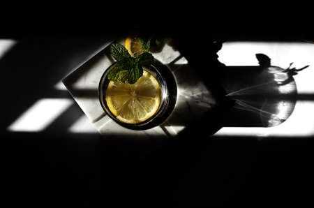 hard light. glass of water with lemon and mint. Imagens