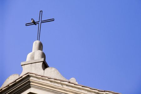 adorning: Bird perched on the cross adorning church roof Stock Photo