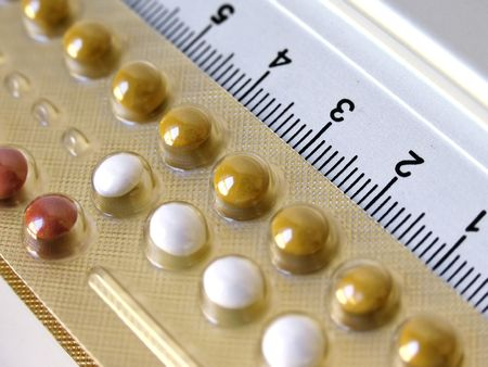 birth control: Packet of birth control pills next to instrument of measure